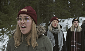 Kolme naislaulajaa ulkona talvella